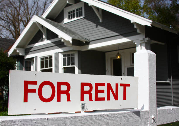 For rent sign in front of gray and white home stock photo
