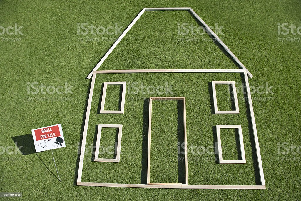 For sale' sign and house outline in grass royaltyfri bildbanksbilder