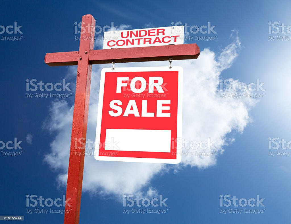 For Sale sign for home in front of blue sky stock photo