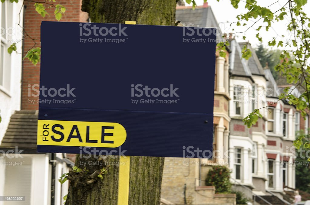 for sale sign with British houses at the backgorund stock photo