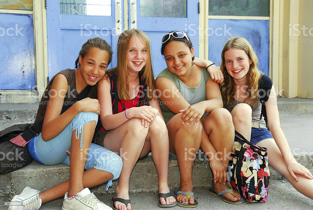 For school age children sitting on a step outside the school stock photo