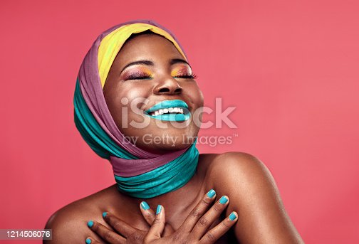 Studio shot of a beautiful young woman smiling while wearing a head wrap and make up against a pink background