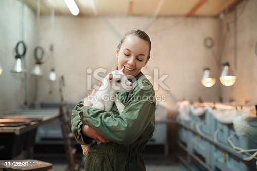 Shot of a young woman holding an adorable baby goat at a dairy farm