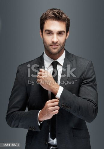 Gorgeous young man doing up his cufflinks and looking at you, isolated on grey - copyspace