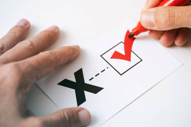 X for the third gender category closeup of a young caucasian person doing a check mark on a paper with a X written in it, for the third gender category cisgender stock pictures, royalty-free photos & images