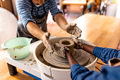 Multi-Ethnic couple at artwork in pottery. Mid adult couple doing creative work in pottery workshop. Creative man and woman as workers or business owners standing at the pottery shop.