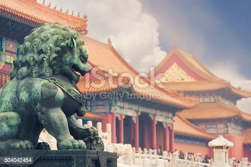 Old imperial lion sculpture in front of historical Forbidden City buildings.