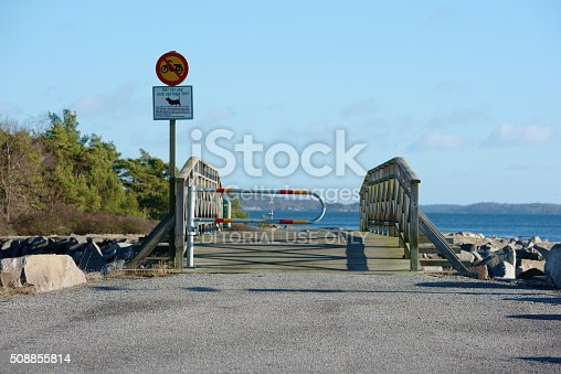 Karlshamn, Sweden - February 04, 2016: Signs telling that it is forbidden to drive mopeds and let dogs loose on the other side of the gate to protect the wildlife. A bridge takes you to the island.