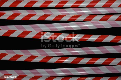 istock Forbidding signal red and white tape on a black background 1132793245