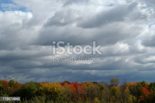 Storm clouds forming over beautiful fall leaves in October in upper New York State.