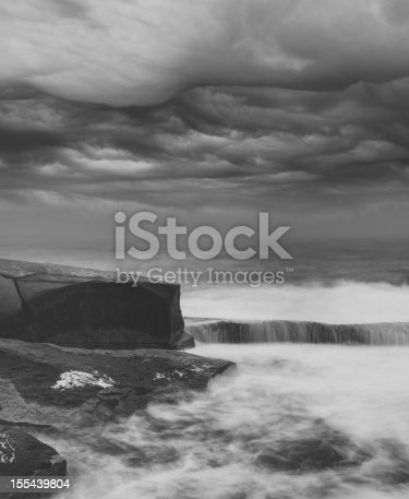 Dramatic seascape with ominous clouds overhead.  Long exposure in light surf, toned black and white.