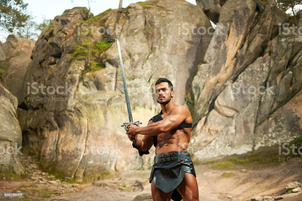 Forceful young warrior with a sword stock photo