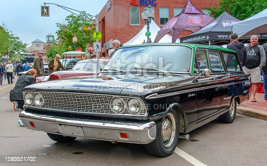 Moncton, New Brunswick, Canada - July 8, 2016 : 1963 Ford Fairlane station wagon parked in downtown area during 2016 Atlantic Nationals, Moncton, New Brunswick, Canada. People walk on the sidewalk and among the classic autos in the downtown area.
