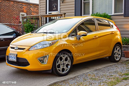 Hamilton, Canada - August 19, 2013: Orange-yellow colored Ford Fiesta hatchback parked on a driveway.