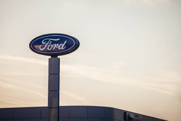 Ford logo on their main dealership store Belgrade. Ford is an American car and automotive manufacturer, the second biggest in the USA Picture of the Ford sign with their logo on their car dealership in New Belgrade, taken at sunset. Ford Motor Company is an American multinational automaker selling automobiles and commercial vehicles insignia stock pictures, royalty-free photos & images