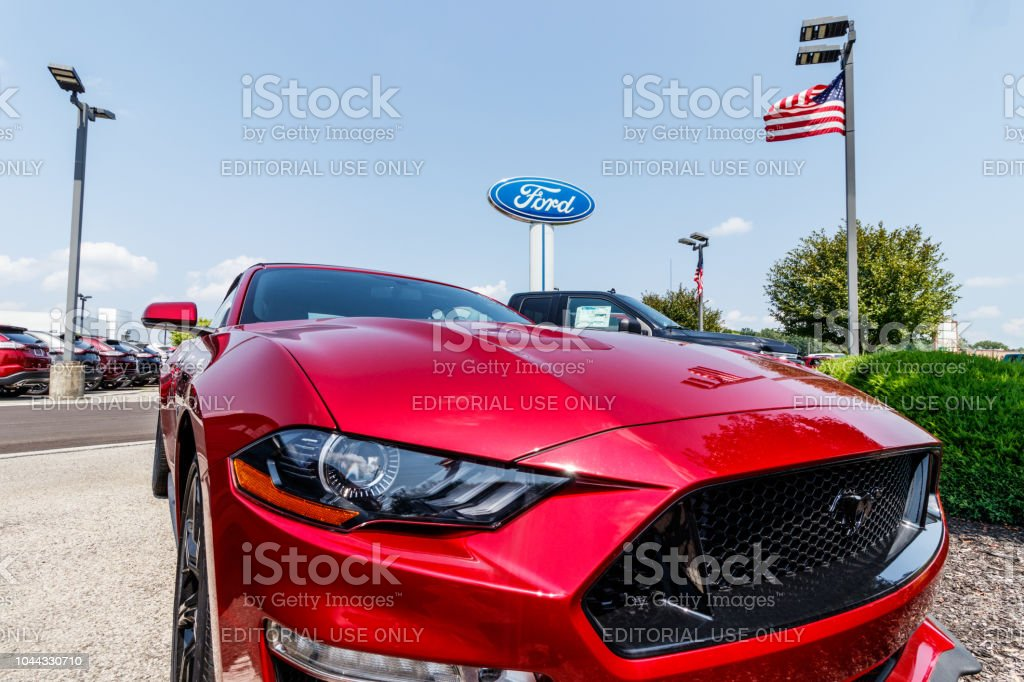 Ford Mustang at a dealership with American flag. Ford sells products under the Lincoln and Motorcraft brands stock photo