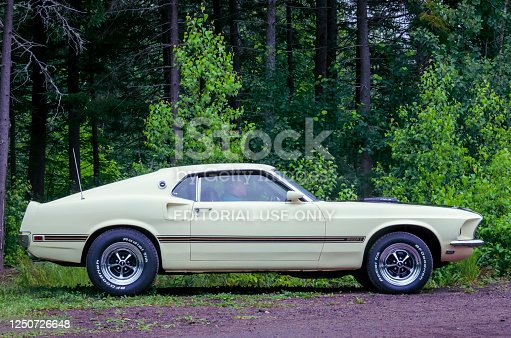 Moncton, New Brunswick, Canada - July 10, 2016 : 1969 Ford Mustang Mach 1 parked at Centennial Park at 2016 Atlantic Nationals  in Moncton, New Brunswick Canada. A man sits in the passenger seat and appears to be waiting.