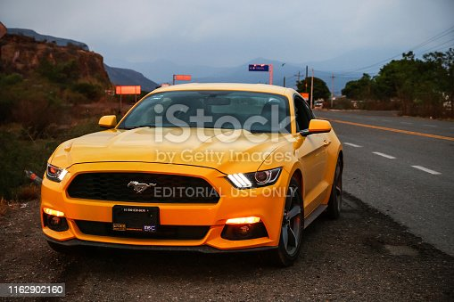 Oaxaca, Mexico - May 26, 2017: Yellow supercar Ford Mustang at the roadside of the interurban road.