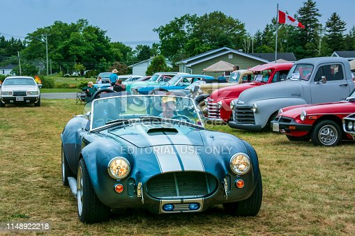 Saint John, New Brunswick, Canada - July 18, 2015 : Man drives his 1965 Ford Shelby replica into the Outkast Car Club's Annual car show on a damp day  in Saint John, New Brunswick.