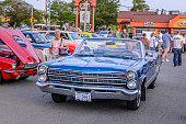 Dartmouth, Nova Scotia, Canada - July 21, 2016 : A senior man driving a 1967 Ford XL convertible enters the weekly summer A&W cruise-in, Woodside Ferry terminal, Dartmouth, Nova Scotia, Canada. A senior woman walks beside the car and gives it a look.