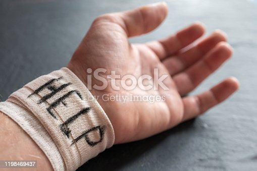 1091817198 istock photo Forearm of a man with a bandage and the word help in English 1198469437