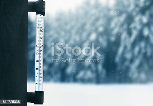 istock forecasting winter weather thermometer on glass window with forest background 614725036