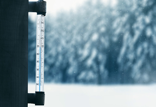 forecasting winter weather thermometer on glass window with forest background