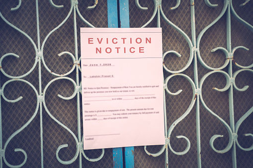 Foreclosed or eviciton notice on a main door with blurred details of a house with vintage filter