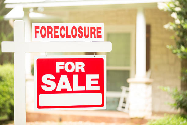 """Foreclosure, house for sale sign. Front yard of home. Nobody. Red and white """"Foreclosure, Home for Sale"""" sign in front of a stone, wood house that is for sale and is being foreclosed upon by a financial institution. Green grass and bushes indicate the spring or summer season. Front porch and windows in background.  Economic depression, recession, bankruptcy concepts. foreclosure stock pictures, royalty-free photos & images"""