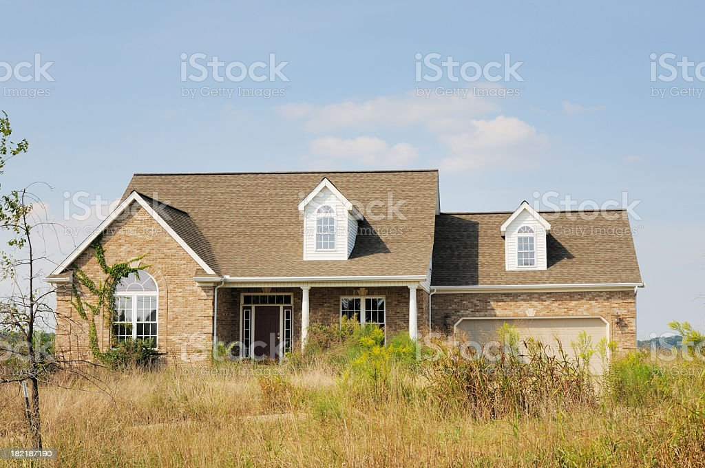A foreclosure modern American home with an overgrown lawn stock photo