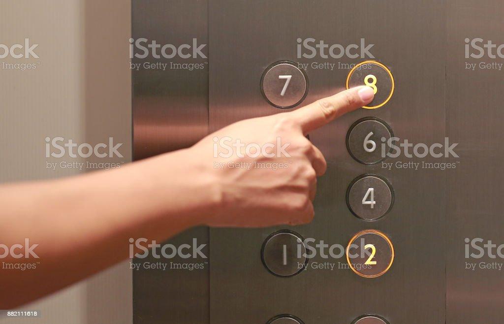 Dedo índice el botón octavo piso en el elevador. - foto de stock