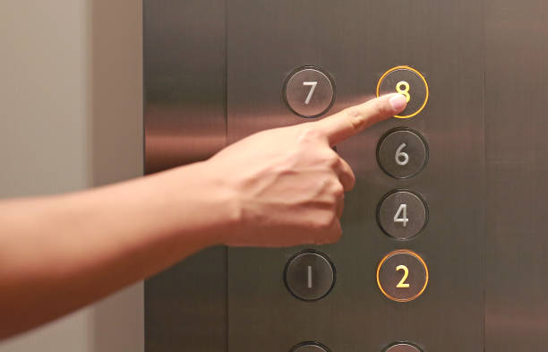 Forefinger pressing the eighth floor button in the elevator. stock photo