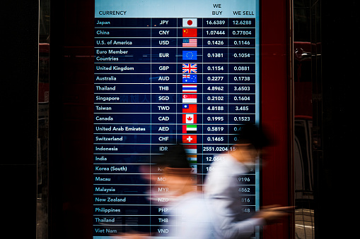 People walk in front of a foreign currency exchange monitor .