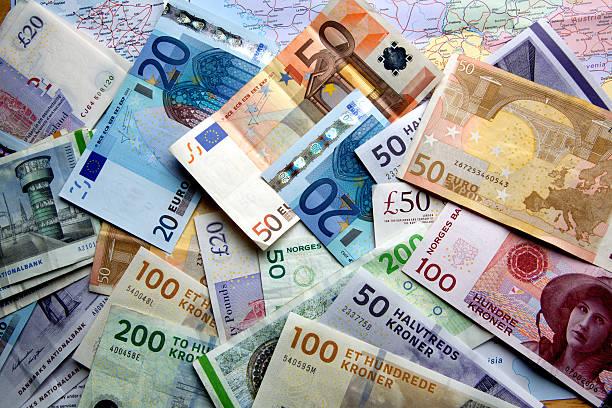 foreign currency scattered over a map - europäische währung stock-fotos und bilder
