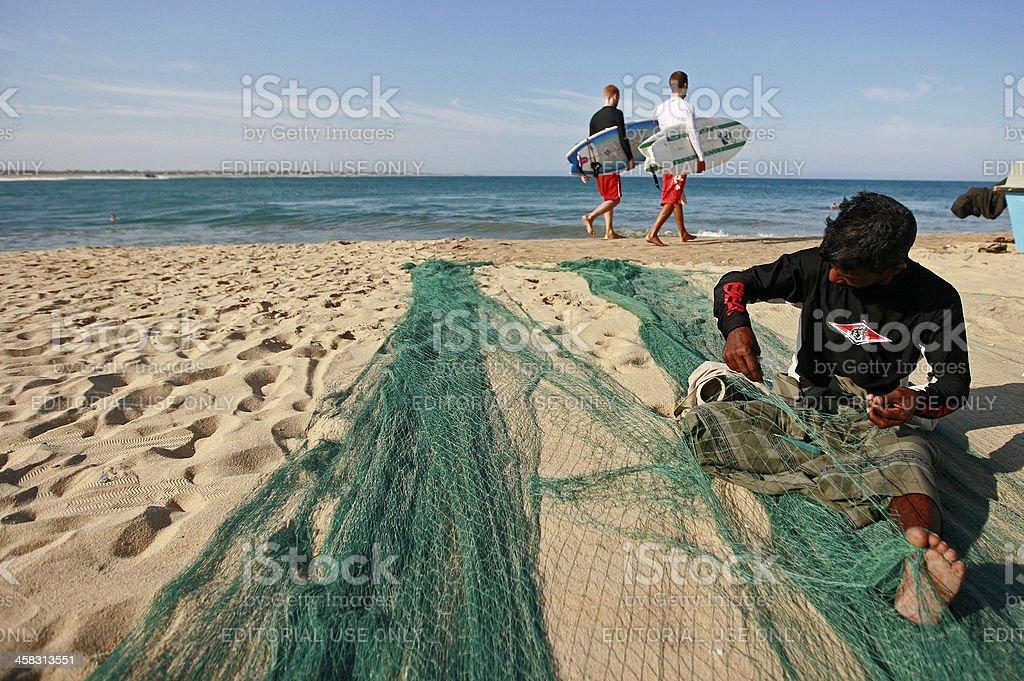 Foreign Surfers walks on beach stock photo