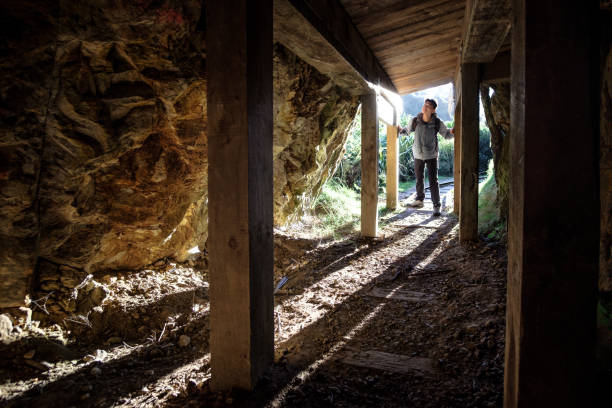 Foreign tourist visitor explores New Zealand Karangahake window walk heritage history site gold mining tunnel stock photo