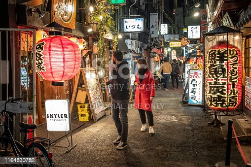 istock Foreign tourists looking for restaurants decorated with traditional old lanterns on back alley street in Namba, Japan. 1164830782