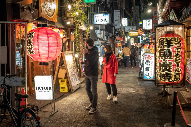 Foreign tourists looking for restaurants decorated with traditional old lanterns on back alley street in Namba, Japan. stock photo