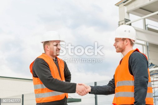 1055059750istockphoto Foreman and construction worker shaking hands 507242777