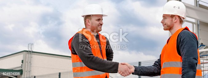 1055059750istockphoto Foreman and Construction Worker Shaking Hands 524924005