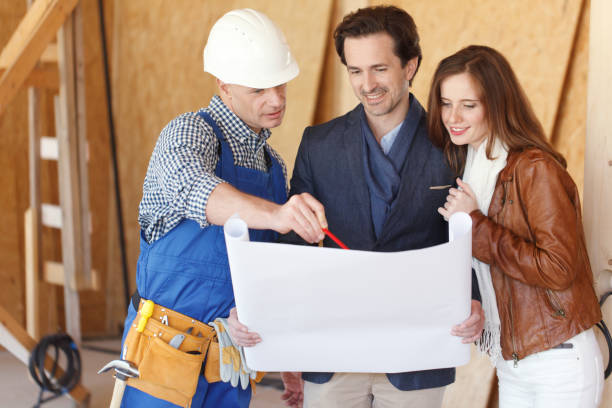 Foreman and couple with blueprint stock photo