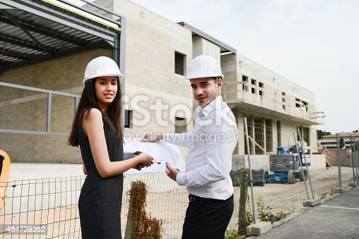 681142982 istock photo foreman architect man woman supervising building construction site with blueprint 484739352