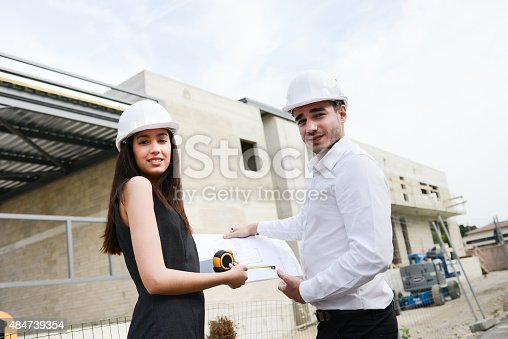 681142982 istock photo foreman architect man woman supervising building construction site with blueprint 484739354