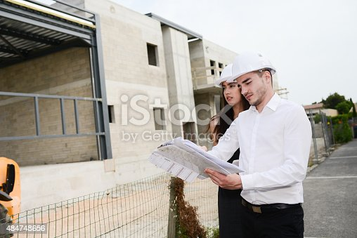 681142982 istock photo foreman architect man woman supervising building construction site with blueprint 484748656
