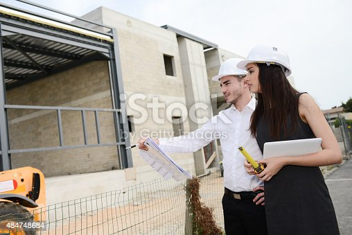681142982 istock photo foreman architect man woman supervising building construction site with blueprint 484748684
