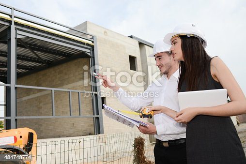 681142982 istock photo foreman architect man woman supervising building construction site with blueprint 484748774