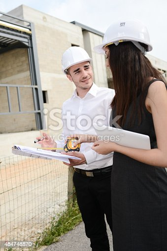 681142982 istock photo foreman architect man woman supervising building construction site with blueprint 484748870