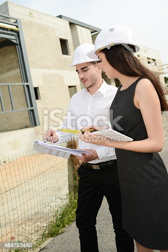 681142982 istock photo foreman architect man woman supervising building construction site with blueprint 484763440