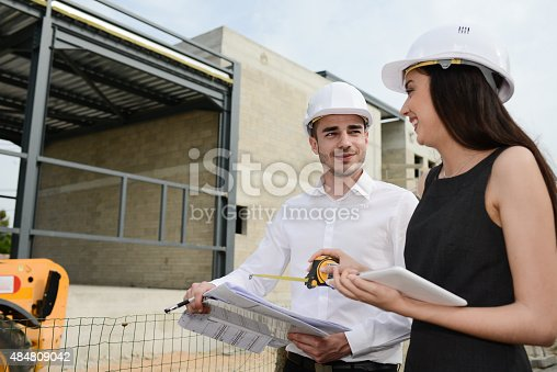 681142982 istock photo foreman architect man woman supervising building construction site with blueprint 484809042