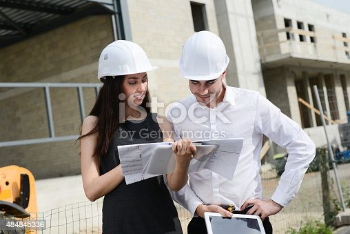 681142982 istock photo foreman architect man woman supervising building construction site with blueprint 484845336